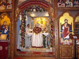 "A coptic priest celebrating ""ad orientem"" behind the iconostasis"
